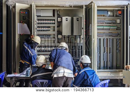 Engineer working on checking and maintenance equipment at wiring on PLC cabinet Engineer checking status step up transformer