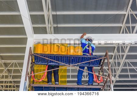 Workers install PVC strip curtain or plastic strip doors around Factory Gate