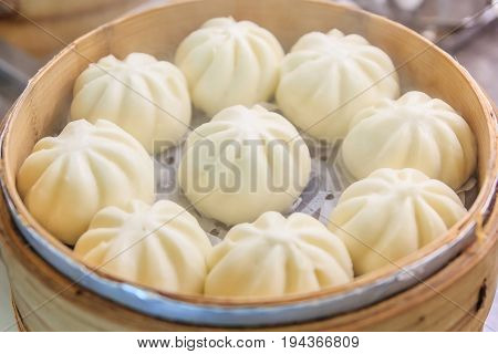 Chinese dumplings(steamed stuff bun) being steamed on the traditional bamboo pan
