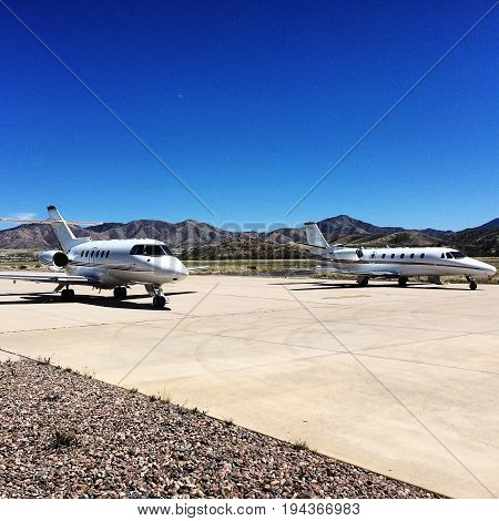 There are two Private Jets in this photo taking to rest at the tarmac and getting ready for their next flight.