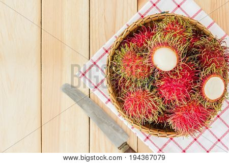 fresh tropical rambutan fruits over basket with knife on wood background Top view with copy space and text.