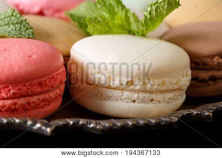 Beautiful colored macaroons macro on a dish. Horizontal background