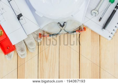 Safety equipment and tool kit on wooden background with copy space. personal safety accessories on surface. Items include a hard hat with safety goggles hammer wrenches