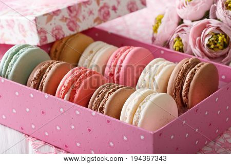 French Macaroons In A Pink Box And Flowers Close-up. Horizontal