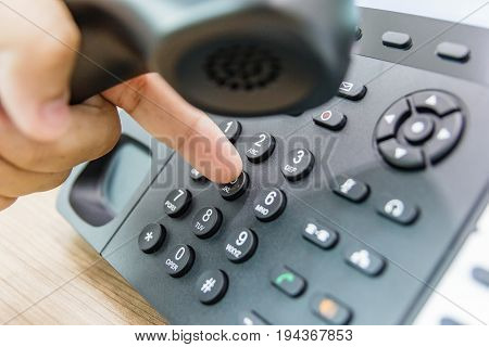 Closeup of male hand holding telephone receiver while dialing a telephone number to make a call using a black landline phone. Conceptual of global communication business support and customer care.
