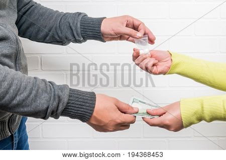 Woman drug addict buys drugs from a man hands close-up