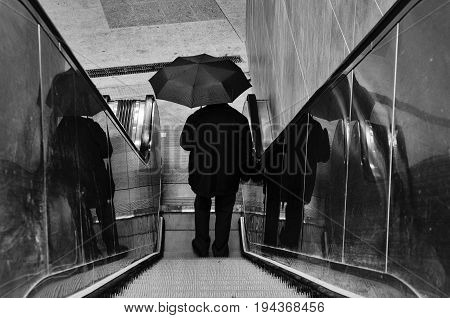 MAN WITH UMBRELLA - Rainy man on moving escalator in underground passage