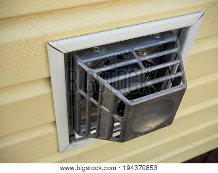 The protective grate of the coaxial flue gas convector on the wall of the house
