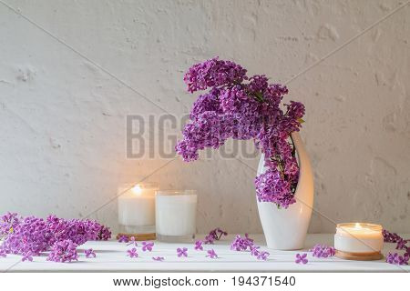 flowers in vase with candles on background white wall