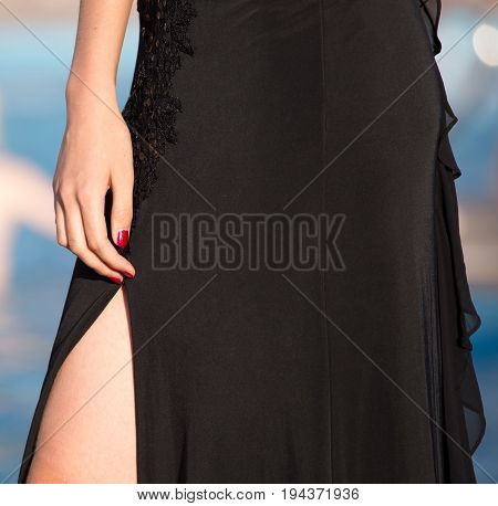Part of a girl's body in a black dress .