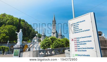 Sign Of Direction In Front Of The Basilica Of Lourdes, France