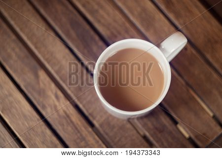 closeup photo of a white cup of tea on a wooden table