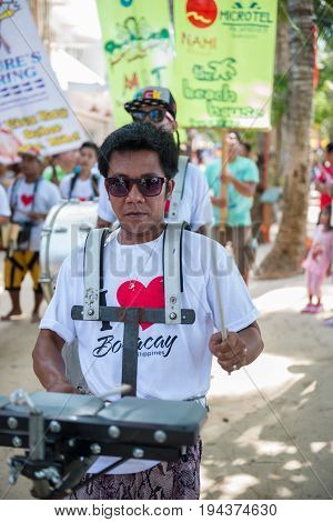BORACAY, WESTERN VISAYAS, PHILIPPINES - JANUARY 11, 2015: Vertical picture of a man playing music in Ati-Atihan Festival at White Beach Boracay.