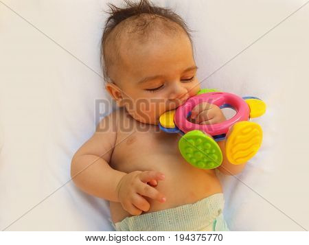 3 months old baby boy playing with teething toy