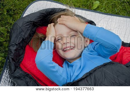 a little girl camping with sleeping bag