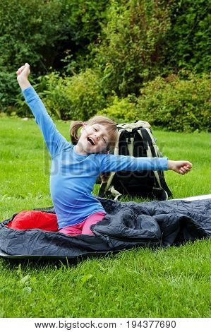 happy little girl resting in a sleaping bag - camping concept