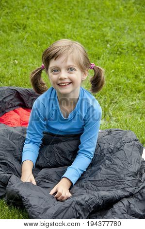 little girl on sleaping bag - camping concept