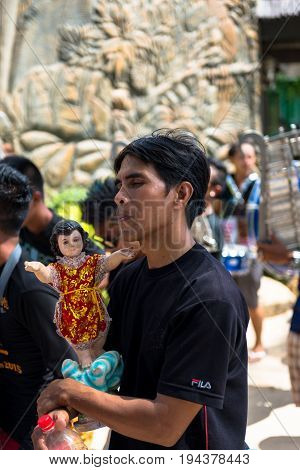 BORACAY, WESTERN VISAYAS, PHILIPPINES - JANUARY 11, 2015: Local man with closed eyes walking with Santo Nino statue during Ati-Atihan Festival at White Beach.