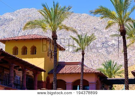 Spanish style buildings surrounded by Palm Trees with rugged mountains beyond taken in Palm Springs, CA