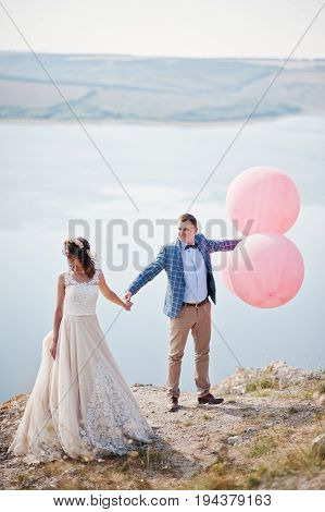 Gorgeous Bride And Groom Having Great Time Standing On The Precipice With A View Of A Lake With Ball