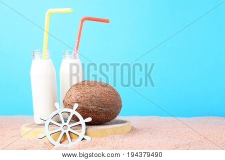 Coconut With Bottle Of Milk And Ship Wheel On Beach Sand