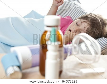 ill little girl sleaping in the bed and drugs inhaler and thermometer