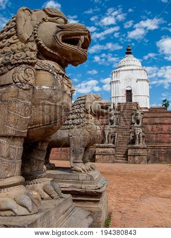 KATHMANDU, BHAKTAPUR, NEPAL: Ancient stone lions and the large white Fasidega Temple dedicated to Shiva in the Durbar Square in Bhaktapur.