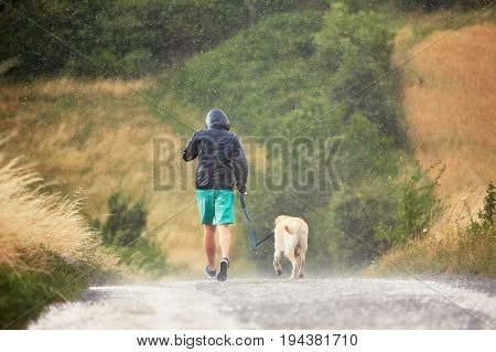 Man With Dog In Heavy Rain