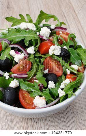 Variation of Greek salad with arugula cherry slices feta and olives