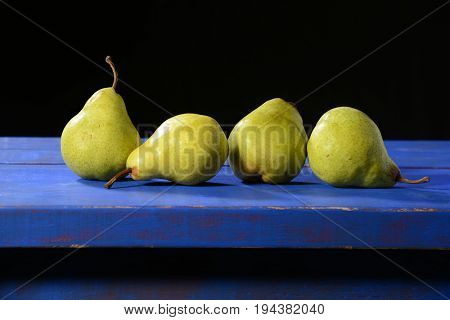 Green pears on a blue rustic table