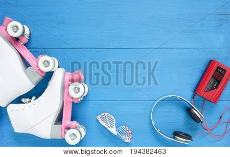 Sport, healthy lifestyle, roller skating backround. White roller skates, sunglasses, headphones and vintage tape player. Flat lay, top view.