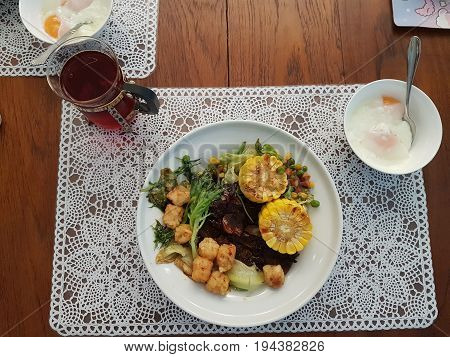 Top view of a complete full meal of meat served with vegetables on white plate with place mat and bowl of half boiled eggs set on wooden table with a drink