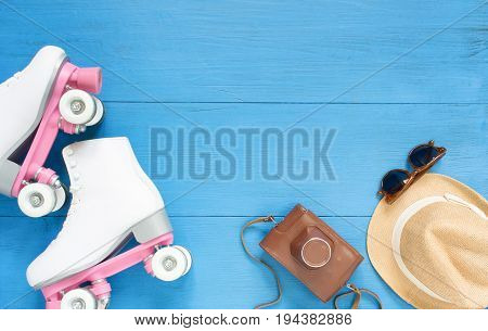 Sport, healthy lifestyle, roller skating background. White roller skates, retro camera, straw hat and retro sunglasses. Flat lay, top view.