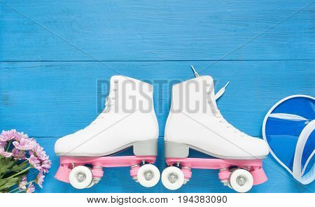 Sport, healthy lifestyle, roller skating background. White roller skates and blue visor hat. Flat lay, top view.