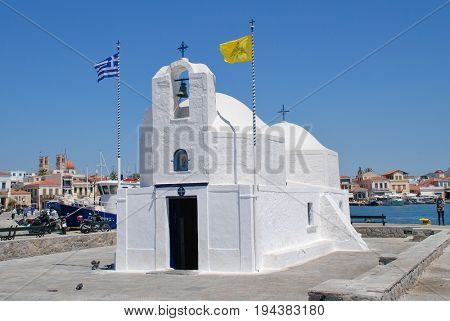 AEGINA, GREECE - APRIL 26, 2017: The whitewashed church of Agios Nikolaos on the harbour front at Aegina Town on the Greek island of Aegina. The island is a popular destination for Athenians.