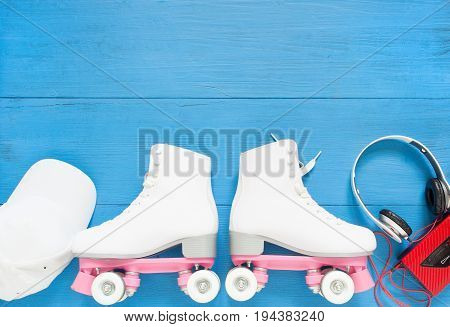 Sport, healthy lifestyle, roller skating background. White roller skates, headphones and white baseball cap. Flat lay, top view.