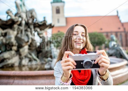 Young woman tourist standing with photo camera on the Alexander square in Berlin