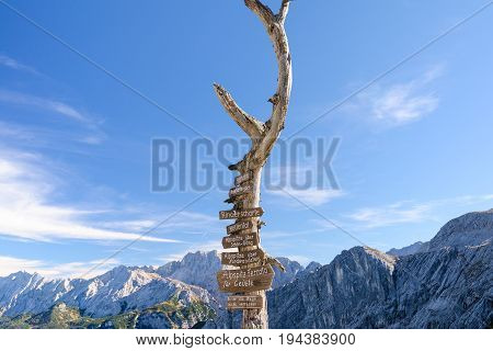 Wooden signpost with route arrows on dry tree in German Bavarian Alps mountains on Alpspitze peak