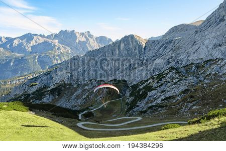 Alpine landscape with soaring paraglider in Bavarian Alps mountains