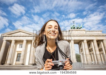 Portrait of a young smiling woman tourist standing with photo camera in front of the famous Brandenburg gates in Berlin