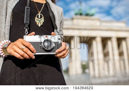 Young woman tourist standing with photo camera in front of the famous Brandenburg gates in Berlin