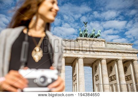 Young woman tourist standing with photo camera in front of the famous Brandenburg gates in Berlin. Image focused on the background