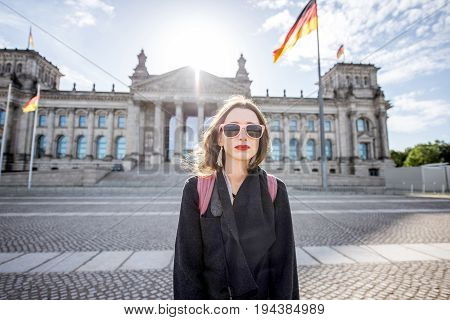 Woman standing in front of the famous Bundestag building in Berlin during the sunrise