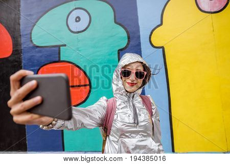 Young woman tourist making selfie photo standing in front of the Berlin wall in Germany