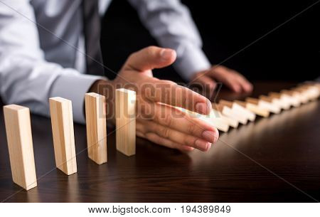 Chain Reaction In Business Concept, Businessman Letting Or Preventing  Dominoes Continuous Toppling On Rustic Wooden Desk poster