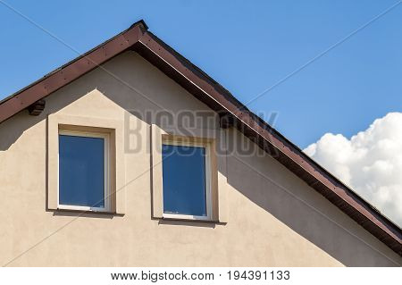 Close up of top windows under roof in house