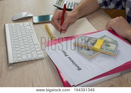 person Man pointing writing goals on a paperwriting business plan at workplace man holding pens papers notes in documents Saving money concept