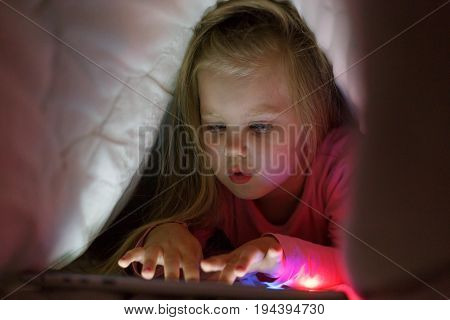Little girl is playing on the tablet in secret from her parents at night under the blanket