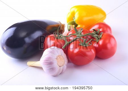 Fresh assorted vegetables eggplant, bell pepper, tomato, garlic. Isolated on white background. Selective focus