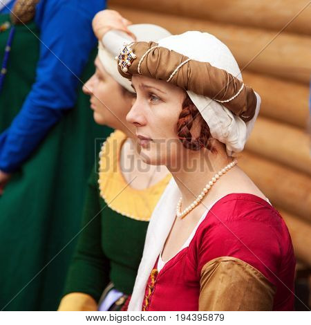 Khabarovsk Russia - June 11 2017: Middle ages period costume - young noble lady wearing red dress a headgear and braids hairstyle. Caucasian woman dressed in historic costume at medieval reenactment